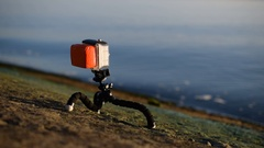 Action camera in plastic case on tripod near blue water Stock Footage