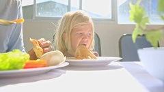 Little Blond Girl Eats Chicken near Mother  at Table Stock Footage