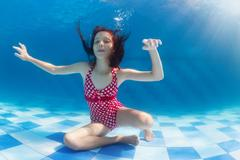 Girl diving underwater in swimming pool Stock Photos