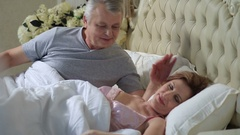 Mature loving couple lounging in bed after awaking Stock Footage