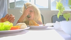 Little Blond Girl Eats Chicken Mother Sets Hair at Table Stock Footage