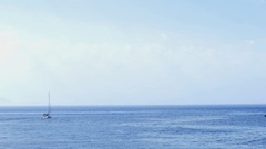 Sailing boat which departs wide rocky shore besides that is seen on bo Stock Footage