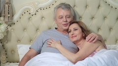 Couple lounging in bed after awaking cuddling Stock Footage