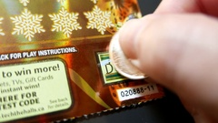 Close up man scratching lottery ticket at bonus section Stock Footage