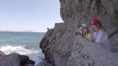 Mother and two little girls walk through mountains along sea. Crimea Stock Footage