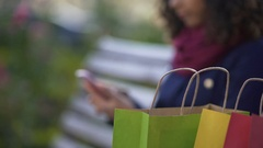 Young woman shopping online on smartphone while sitting on bench outdoors Stock Footage