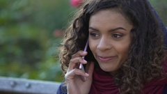 Happy mixed race woman talking over smartphone outdoors, smiling, ending call Stock Footage
