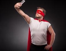 Super hero man with laptop computer Kuvituskuvat