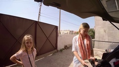 Two little girls put things in trunk of blue car. Cottage in the summer Stock Footage