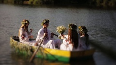Three girls and a guy in the Slavic national dress floating in a boat. Girls in Stock Footage
