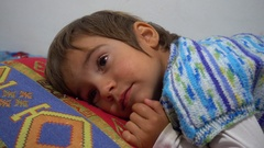 Unhappy child face in to cushion Stock Footage