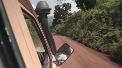CLOSE UP: Safari jeep game driving tourists in lush African jungle on dusty road Stock Footage