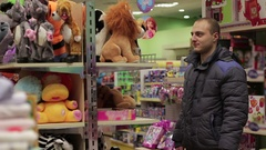 Dad chooses a soft toy in the store Stock Footage