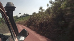 CLOSE UP: Safari jeep game driving tourists in lush African jungle on dirty road Stock Footage