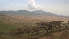 CLOSE UP: Driving past Maasai village with traditional houses on mountain slope Stock Footage