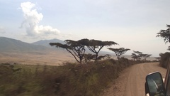 CLOSE UP: Touristic safari jeep descending into breathtaking Ngorongoro Crater Stock Footage
