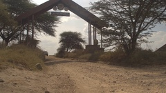 CLOSE UP: Safari jeep entering Serengeti National Park gate starting game tour Stock Footage