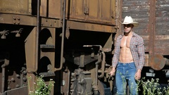 Muscular cowboy, open shirt on naked torso, walking by old train Stock Footage