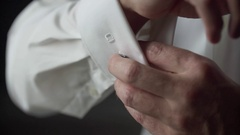Man buttons up cufflinks on white shirt Stock Footage