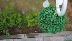 Decorative green ball hangs over the pavement Stock Footage