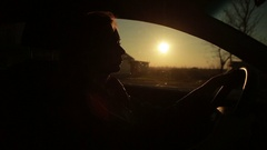 Blondie young woman driving a car. silhouette in sunset Stock Footage