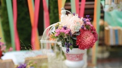 Table decorated with wooden lettering love, white bird cage and flowers stands Stock Footage