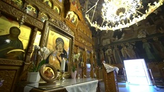 Golden icon stands on wooden table before iconostasis Stock Footage
