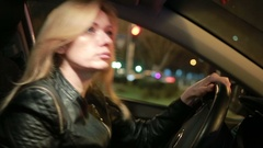 Blondie young woman driving a car in night Stock Footage