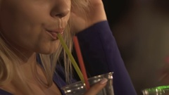 Attractive young female drinking a cocktail, flirting and smiling at nightclub Stock Footage