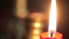 Putting out a burning candle with a tool Stock Footage