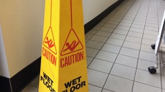 Camera Pans down a Caution Wet Floor Sign on Tiled floor Stock Footage