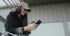 Cute brunette girl with baseball cap holding credit card and using her smart Stock Footage