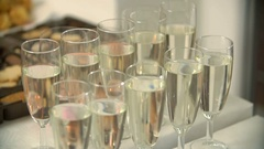 Full champagne flutes stand on white table Stock Footage