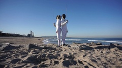 A man and woman fencing on the beach, slow motion. Stock Footage