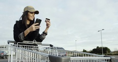 Cheerful brunette girl holding credit card and using her smartphone in front of Stock Footage