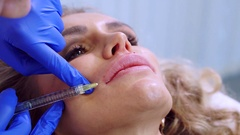 Beautician make injection plastic lips. Young woman on lip Augmentation in a Stock Footage