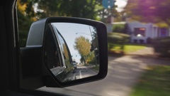 Driving on a typical small American town. In the frame of the rear-view mirror Stock Footage