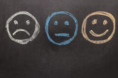 Drawing Unhappy and Happy Smileys on Blackboard Stock Photos