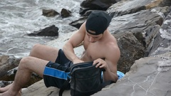 Young Man Using Cell Phone Sitting at Beach Stock Footage