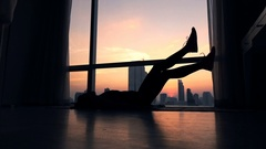 Silhouette of woman doing scissors exercise on floor by window at home Stock Footage