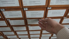 Hand opens drawer and browse with fingers through cards arranged alphabetically Stock Footage