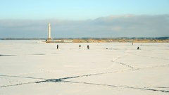 Silhouettes of fishermen walking on frozen water reservoir Stock Footage