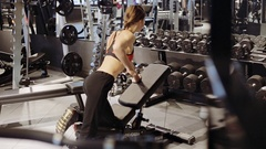 Young woman lifting some weights and working on her triceps in a gym Stock Footage