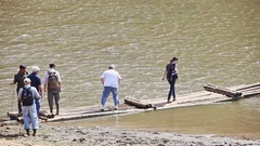 Caucasian Tourists Board Large Wooden Raft on Lake Bank Stock Footage