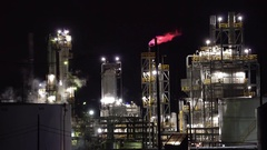 Smoking oil refinery plant with flame at night - United States Stock Footage