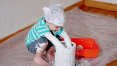 Little cute boy kid dunks hands in paint can painting wall at home Stock Footage