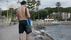 Young Man Undressing at Beach Stock Footage