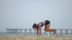 A young woman doing burpees while working out on the beach , slow motion. Stock Footage