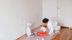 Little boy kid with mother painting a wall at new home. pours paint Stock Footage