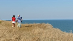 4K. Adult attractive couple walk against  sea in summer day     Stock Footage